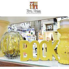 Decoração com a cor amarela com castiçal, vaso, escultura book