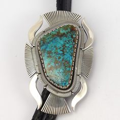 Heavy Gauge Sterling Silver Bola Tie with a Ketoh Style Shape and set with a Large Natural Pilot Mountain Turquoise Stone and with Intricate Stamped Designs. This bola tie features a black leather cor