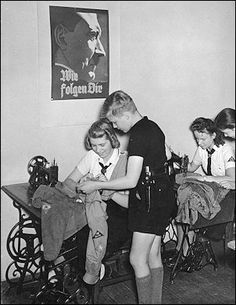 """""""Ladies from the league of German girls help out a member of the Hitler Youth with his uniform repairs."""