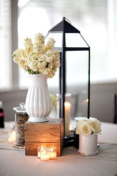 Love how this is displayed. With the wood block to add height, and the contrast with the tall hurricane and short vase of flowers. Love the wild rice too, gives it a nice color and texture. Just love this display for ambiance and decor! The only think i'm not crazy about the white vase.