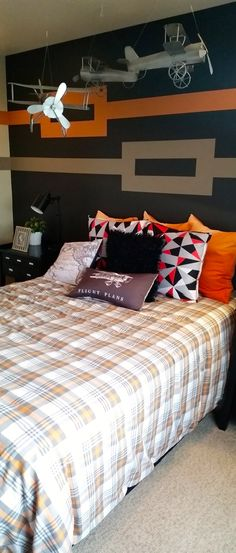 Dark #paint like #black can be a great base color in a #boy's #bedroom. Adding simple, geometric patterns using accent colors like orange and tan can break up the base color with dramatic effect. Brighten the mood with light colored bedding and personal touches like #plane #models and posters.