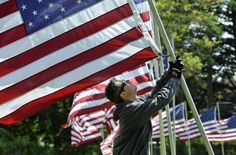 Frequent flier: Ethan Breithaupt sets flag No. 596 into position at Fairmount Memorial Park on Tuesday in Spokane. Crews are placing nearly 2,300 American flags this week throughout the cemetery as part of their annual observance of Memorial Day. Photo by Dan Pelle, The Spokesman-Review. #spokane