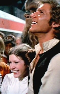 D'aww, look at them then. My favourite part of this scene: they're grinning at Luke climbing out of his X-Wing after they've won the Battle of Yavin.