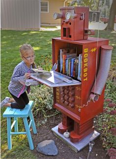 Isabel McNamara looks at a book that is available in a Little Free Library designed to look like a robot and displayed in Oshtemo Township, Mich.