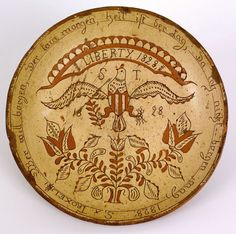 "Montgomery County, Pennsylvania sgraffito redware dish by Samuel Troxel, dated 1828, with central spread winged eagle beneath a banner, inscribed ""Liberty"" and above a potted tulip vine, inscribed verso ""Samuel Troxel Potter 1825"", 11 1/2"" dia. For a similar example, see Garvan, The Pennsylvania German Collection, fig. 143. Provenance: Descended in the family of Arthur Sussel."