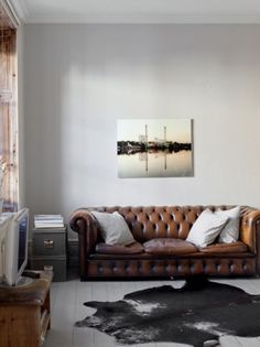 A leather couch and striped pillows