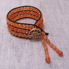 Orange Crackle! The cuff is finished off with a gorgeous acrylic coat bead and two dangles of crackle beads.    Fits comfortably up to an 8 1/4'' wrist.    $35.00