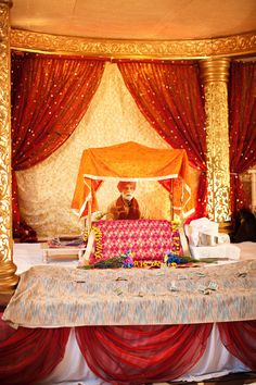 This is an example of the inside of a Sikh temple where the wedding ceremony takes place. The bride and groom along with guests sit below and before the Guru Granth (it is similar to the holy Bible) listen to prayers, songs and blessings all morning until lunch.