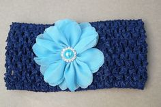 Faixa de crochê, com elastano, azul marinho com flor azul clara de chiffon e miolo de pérola azul.  Serve desde bebês até adultos. R$ 17,00