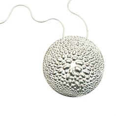 Sterling Silver circle pendant reminiscent of pebbled beaches and sand dollars on adjustable 18-inch Italian chain
