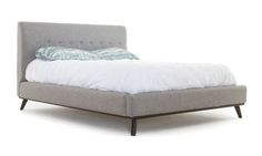 Head off to dreamland in high style with this elegantly button-tufted Mid-century Hopson platform bed. A row of elegant button tufting adorns the tall headboard and a wooden base and slanted legs lend iconic modern hallmarks from head to foot. Choose from three expansive sizes and customize the Hopson to your unique taste with your choice of three wood stains and premium upholsteries to match your dream retreat.
