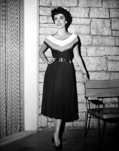 From the wardrobe created by Helen Rose for The Girl Who Had Everything, Elizabeth Taylor models a navy wool skirt with unpressed pleats worn with a blue jersey middy blouse trimmed with white collar banded in red silk