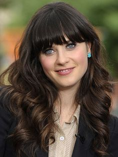 Zooey Deschanel - The New Girl star softens her signature blunt bangs with glossy, buoyant curls. Simple blue-hued studs add femininity to the look while making her eyes pop.