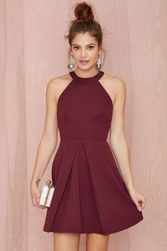 Looking for the ultimate holiday dress? This structured burgundy dress by Keepsake has a cutaway neckline, pleating at skirt, cutout at back, and button/zip closures.