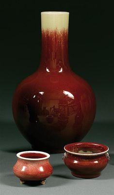 """LOT DE DEUX BRÛLE-PARFUMS en grès porcelaineux et couvertes monochromes rouge, dites """"sang de bœuf"""", reposant sur un piétement tripode, et sur un petit talon, les panses sphériques méplates, l'une dotée de prises en forme de têtes de monstres. (Fêlures à une ouverture). Chine, dynastie Qing, XIXe siècle et vers 1900. Two sang-de-bœuf glazed censers, Qing dynasty, late 19th and ca. 1900. Haut. (max) 7 cm/H. (max) 2 3/4 in."""