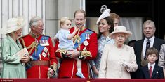 Prince George waves from Buckingham Palace balcony flanked by father Prince William, mother Kate, the Duke and Duchess of Cornwall, the Queen, Prince Andrew and Prince Harry, pictured in the background, in his first official appearance on British soil