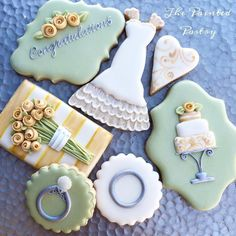 Wedding cookie set:- graceful fitted, lace-trimmed wedding gown; yellow rose bouquet as fresh as spring; wedding and engagement ring set; and a contemporary wedding cake perched on a pedestal - all expertly crafted by The Painted Pastry and posted on Cookie Connection