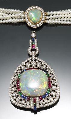 An opal, cultured pearl, synthetic gemstone and diamond pendant-necklace cultured pearls measuring approximately 2.25-2.50mm, suspending a cushion-shaped opal measuring approximately 21 x 21mm, bordered by synthetic square-cut rubies, emeralds, sapphires and round brilliant-cut diamonds; estimated total diamond weight: 1.85 carats; mounted in eighteen karat bicolor gold.