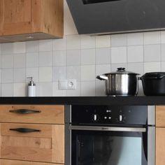 Friesische Fliesen in 9 verschiedenen Weißtönen, kombiniert mit Holztüren und eine schwarze Arbeitsplatte.