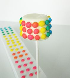 Marshmallow Pop dipped in vanilla candy melts and adorned with candy buttons.