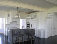 White kitchen with dark hardwood floors, globe lights, trabsom windows and open to living room. Our Town Plans