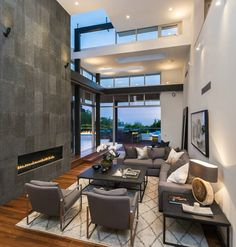 Two story living room stands lush hardwood flooring and muted grey contemporary seating next to an immense slate grey fireplace wall. Patio corner is nearly all-glass, for expansive views and open design.