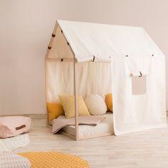 Une chambre d'enfant poétique. Clairsemé d'une ribambelle de coussins poudrés, cette cabane au design épuré deviendra le plus poétique des coins repos pour les enfants au cœur de la chambre