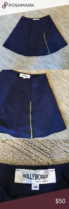 Brand new navy mini skirt with black zipper Never before worn, beautiful and comfortable polyester navy blue mini skirt. The waist band stretches for comfort. There is a black and silver zipper going down one side of the skirt for decoration. So cute for all year round, can be dressed up with heels or down! Hollyworld Skirts Mini
