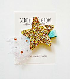A sparkly North Star, with tulle! Attached to a ribbon lined alligator clip or elastic headband.
