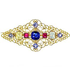 Antique Sapphire Ruby Diamond Brooch. This brooch signed Carlo Giuliano is in 18kt yellow gold. It features two diamonds weighing 2.5cttw, 2 rubies weighing 0.70cttw, and 5 sapphires weighing 3.5cttw. c 1880