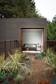 A guest bedroom, with furniture from Room & Board, overlooks the bridge above the dining courtyard. The home's landscape architecture is by Ventura, California–based Jack Kiesel. Photo by Coral von Zumwalt.  Courtesy of: Coral von Zumwalt | Tiny Homes