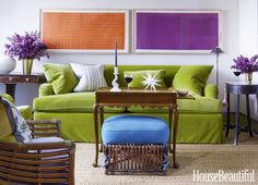 Two paintings by Dan Walsh hang above a custom Bridgewater sofa, upholstered in Designers Guild's Cassia.