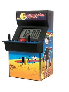"""Arcade Machine Alarm Clock by Paladone. $7.23. The Arcade Alarm Clock is the best way for video game fans to wake up in the morning. Featuring classic arcade sound effects, this retro alarm clock will wake all gamers from their dreams and make them think of Space Invaders and Pac-Man before getting to school. With this arcade alarm, they'll be ready for another day of gaming. This clever alarm clock features a big red snooze ball, an alarm-set joystick, and """"P..."""