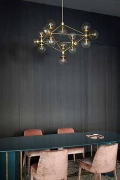 Moody dark dining room with pink velvet chairs, an elegant and modern golden chandelier and a large table.