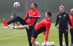 Rio Ferdinand and Jonny Evans of Manchester United compete for the ball as David Moyes the manager looks on during a training session at the Aon Training Complex on March 31, 2014 in Manchester, England.