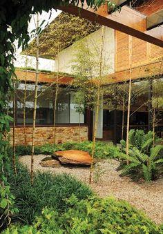 Ipês amarelos e pedriscos conformam o jardim aerado, que pontua a piscina e a área de lazer
