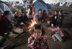 A migrant child eats as others sit around a fire in a railway repairs hangar where people ...