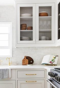 White kitchen features white cabinets accented with chicken wire cabinet doors adorned with white knobs and brass pulls paired with white marble countertops and white staggered tile backsplash.