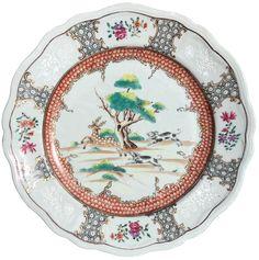 Assiette à décor d'une chasse aux cerfs en porcelaine de Chine de la Compagnie des Indes d'époque Qianlong La scène, dans un cartouche polylobé, est entourée d'un nid d'abeilles en brun-rouge sur couverte. Sur l'aile, des cartouches renfermant des fleurs en polychromie rose ou en bianco-sopra-bianco.