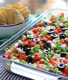 Go big with this 8 layer taco dip recipe - it is the perfect appetizer for large crowds. It's full of meat, cheese, cream cheese, veggies and more.