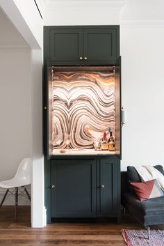 A cocktail cabinet between the kitchen and living room is lined in Swirls wallpaper by Robert Crowder, chosen by the project's interior designer. At the top of the cabinet, Roberts concealed a motion-activated LED strip light from Ikea.