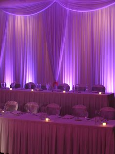 Gorgeous head table backdrop with curtains and uplighting.  #uplighting #wedding #headtable #curtain