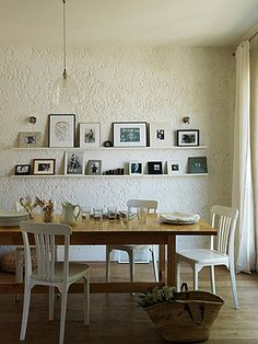 Clear lampshade, textured wall, frames on wall shelf