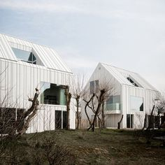 White aluminium panels joined by standing seams create a ridged pattern across the homogenous surfaces of these duplex houses in Belgium