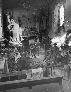 GIs take a rest inside the heavily damaged church in the newly recaptured town of St. George D'Elle weeks after the invasion of Normandy, July 1944