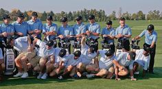 Billy Foster, left, caddie for International team player Branden Grace, knocks over other caddies as steps in for a team photo for the Presidents Cup at Muirfield Village Golf