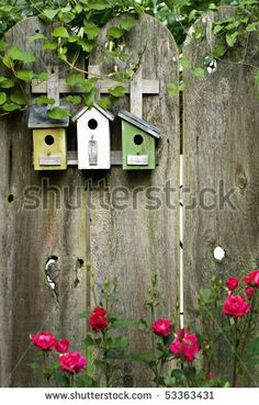 Three birdhouses on old wooden fence - stock photo