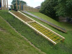 Playground on top of a slope - climbing wall and embankment net on hill going up to play area