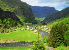 One of the most beautiful train rides in the world goes from Myrdal to Flam, Norway.  Winding steeply down  with views of cliffs, waterfalls and the valley and river below, the train passes through several long tunnels and has views out the windows at every bend.  This shot was taken through the window of the moving train and shows one of the small towns along the river.  We were fortunate to have sun that day.  The next day it rained.   Here's a link to the web site for the train ride…
