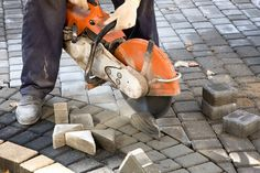 Photo about Working sawing pieces of paving slab on, Man cutting control groove in concrete paving. Image of cement, brick, builder - 11806994 Concrete Saw, Concrete Paving, Paving Slabs, Small Saw, Stone Landscaping, Cool Art, Awesome Art, The Selection, Brick